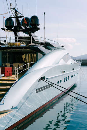 Right side of an expensive blue yacht moored at the pier in Lustica Bay in Montenegro. Imagens