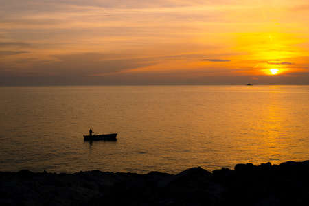 A fisherman on a boat near the shore against the backdrop of a golden sunset.
