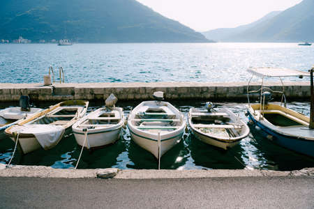 Close-up of fishing boats at the pier of the city of Perast against the backdrop of mountains and blue sky.
