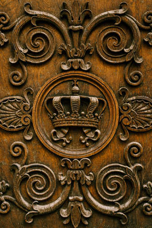 Close-up of carvings in wood - crown and curls. Imagens