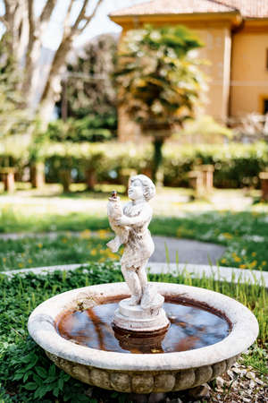 A small garden fountain in the form of a figurine of a child with a fish in his hands in the yard. Imagens