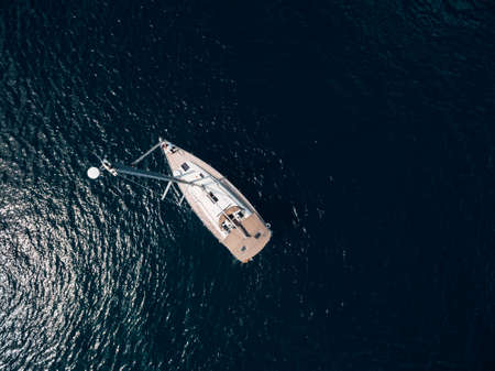 Aerial top view of a sailing yacht with a high mast floating on the water.