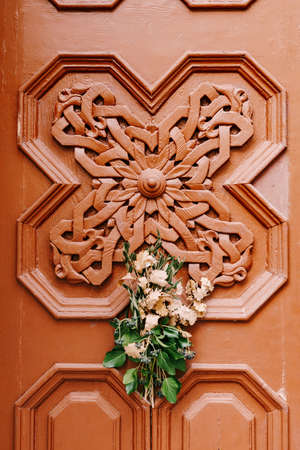 Wooden door with handmade pattern. A bouquet of oak branches and olives is a symbol of Christmas Eve in Serbia, Montenegro, Bosnia and Croatia. Imagens