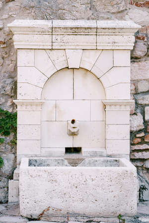 A tiled drinking fountain with a stone bowl in a cobblestone wall.