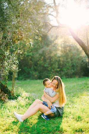Mother is hugging her son while sitting on the grass under an olive tree Banque d'images