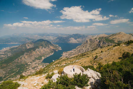 A man and a woman are holding hands on the observation deck, a panoramic view of the Bay of Kotor opens in front of them