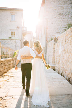 The bride and groom are hugging each other along the streets of Perast next to white brick houses, back view