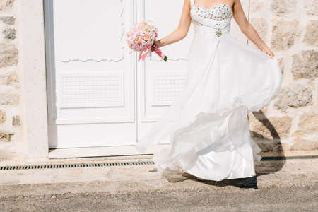 A bride in a stylish wedding dress and with a bridal bouquet stands at the beautiful white door of an old stone house
