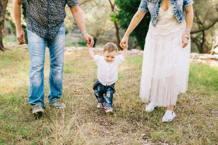 Happy family - mom and dad hold little son by the arms in the olive grove, close-up