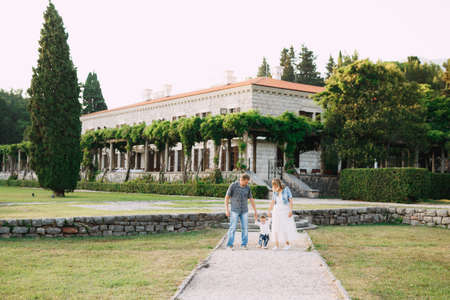 Mom, dad and little son are walking along the path near the beautiful Villa Milocer, parents hold the childs hands