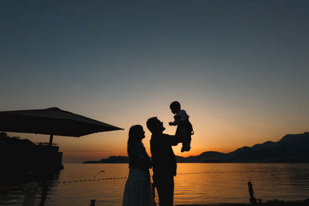 Mom, dad and their son together by the sea at sunset, dad picks up the baby in his arms Banque d'images