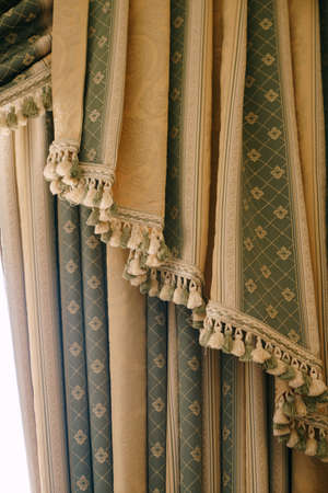 Expensive green and gold curtains with bells close up. Floral fringed curtains at the hotel. Banque d'images