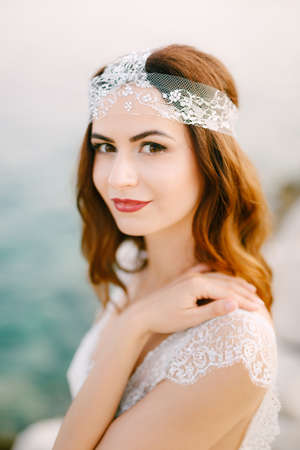 The bride by the sea looks into the frame with her hand on her shoulder, close-up