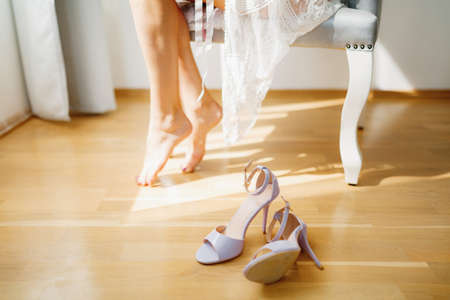 Barefoot bride sits in a chair in a hotel room during wedding preparations, sophisticated sandals are on the floor