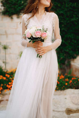 A bride with a bouquet in her hands stands at the wall of a house with a green liana and orange flowers, close-up