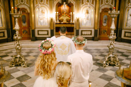 The priest, the groom and the bride in wreaths stand at the altar of the Church of St. Nicholas in Kotor during the wedding, back view