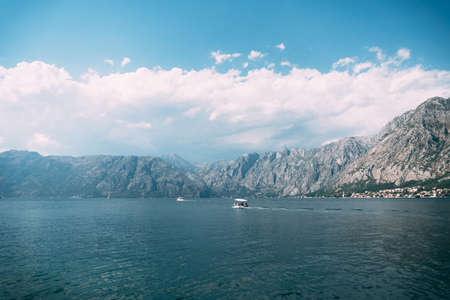 White motor boat is sailing along the Kotor bay against the background of mountains