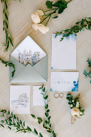Wedding rings lie on the tile floor, surrounded by watercolor paintings, green twigs and flowers. The paintings depict old houses Imagens