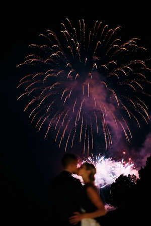 Kissing couple on the background of fireworks in the night sky