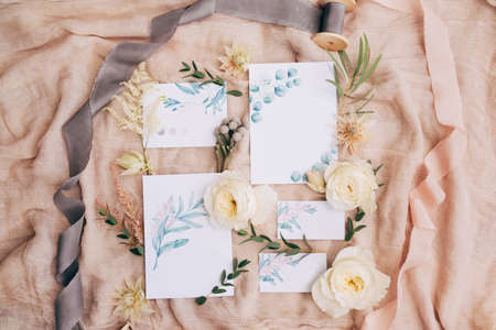 Watercolor paintings, ribbons, roses, green twigs and wildflowers lie on a beautifully spread canvas. The pictures show the stems of flowers