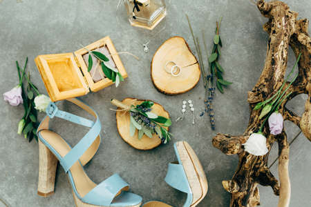 Wedding rings lie in a wooden stand surrounded by sandals with heels, wooden box, perfume, flowers and twigs on the floor