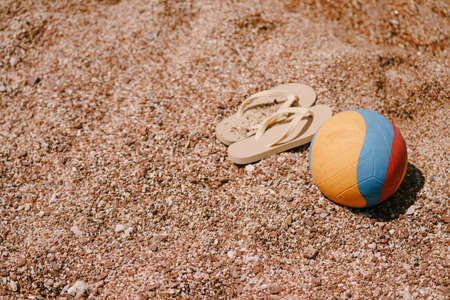 Multicolored ball and beige flip flops lie on the beach
