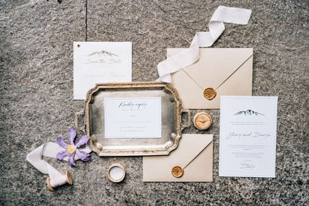 On the stone slab are wax-sealed envelopes, a metal tray, ribbons, flower and postcards. Top view Imagens