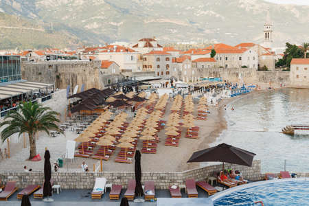 View of the small beach of the old town of Budva, Montenegro against the backdrop of green mountains. There are sun loungers on the beach under sun umbrellas Imagens