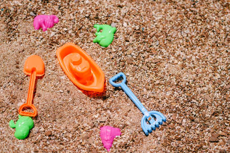 Multi-colored plastic kids beach toys lie on the sand Imagens