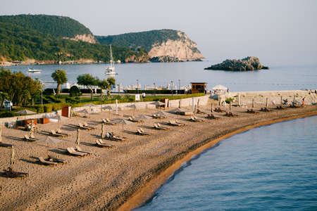 View of a narrow beach with sun loungers and sun umbrellas in Montenegro