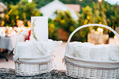 Blank card with ornament stands on rolled towel in white wicker basket on table. Wide angle Imagens