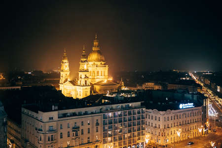 Basilica of St. Stephen in the light of artificial lighting in the ensemble of neighboring buildings Imagens