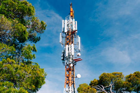 Cell tower against the background of green trees and blue sky. Close up