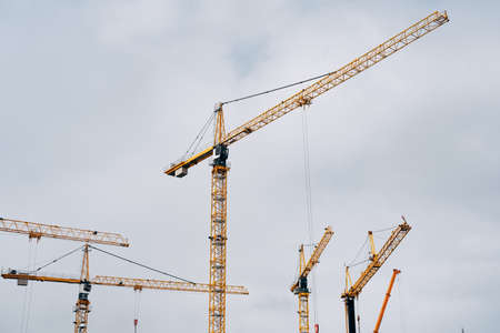 Yellow cranes against the blue sky. Construction background.