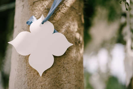 White paper decorative flower hanging from a ribbon on a pillar. Wedding decorations Imagens