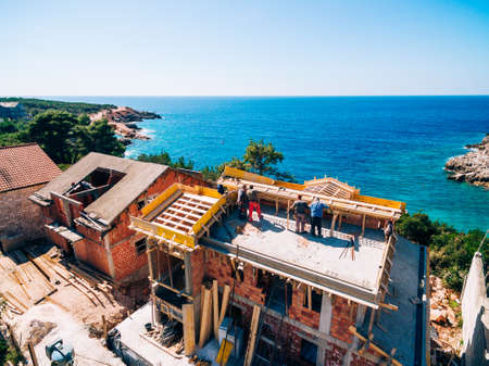 Construction site of a house. View from a drone in the background of the sea
