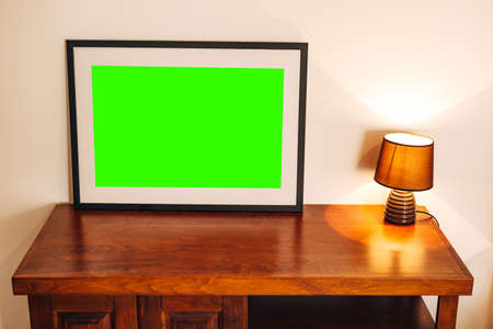Empty painting in a black frame stands on a wooden table near a glowing night light