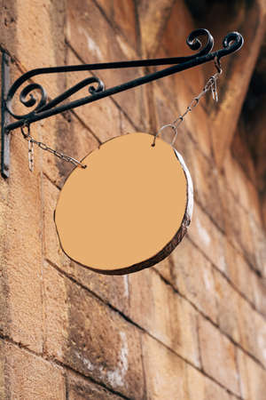 Round wooden blank signboard hanging on chains on a forged pin on an antique stone wall