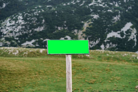 Rectangular blank sign on the road with snow-capped mountains in the background Imagens