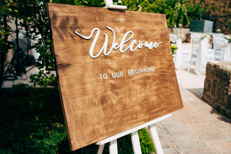 Brown wooden easel with an inscription. Inscription: Welcome to our beginning