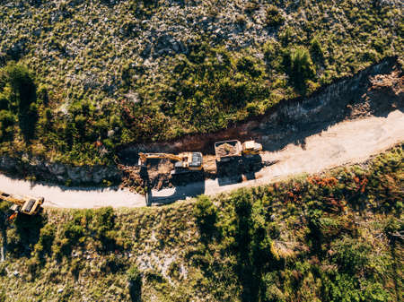 Yellow tracked tractor loads a quarry vehicle with sand. View from above