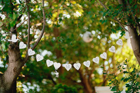 Garland of white hearts and doves stretched between green trees
