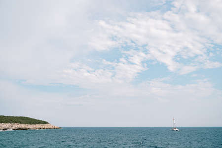 Blue sky with white clouds. Catamaran floats on the sea in the distance