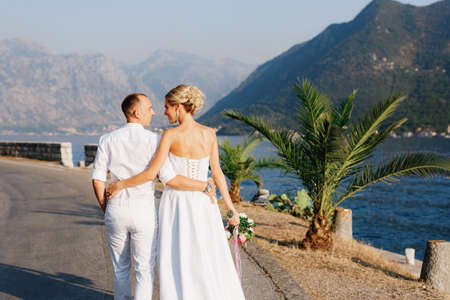 The bride and groom walk along the pier near the old town of Perast, hugging each other, back view Imagens