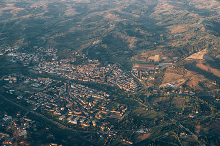 View from the airplane window of the green mountain ranges and the city in the Tuscany region