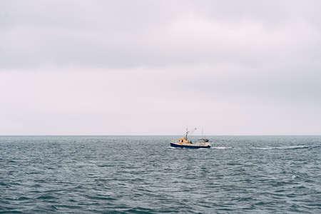 White fishing boat floats in the Atlantic Ocean near Iceland