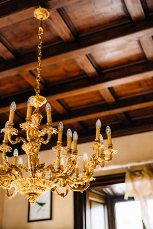 Close-up of an antique gold chandelier in the interior of an old villa.
