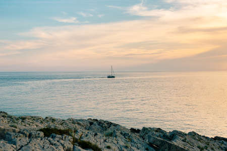 Sailboat is sailing far out in the sea against the backdrop of a sunset. View from the rocky shore Imagens