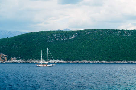 White two-masted schooner sails along the rocky coast against the backdrop of mountains
