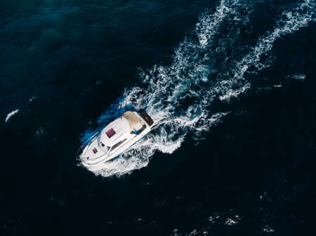 White motorboat floats on the open sea. View from above Imagens